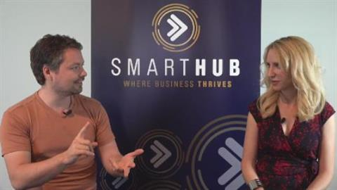Photo of Daniel Johnsen talking to Elize Hattin with the SmartHub banner behind them