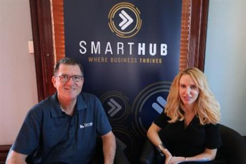 Photo of David French and Elize Hattin sitting in front of the SmartHub banner