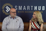 Simon Lever and Elize Hattin sitting on a couch in front of SmartHub banner