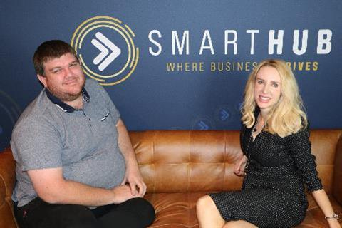 Photo of John Cook and Elize Hattin sitting on a tan coloured couch in front of SmartHub Rockhampton logo